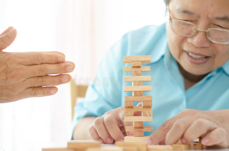 Elderly activities. Asian elderly woman Wearing a blue shirt And friend are playing games Have fun in the morning at home in the room stock photos
