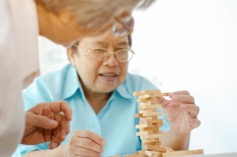 Elderly activities. Asian elderly women Wearing a blue shirt And friend are playing games Have fun in the morning at home in the room royalty free stock photography