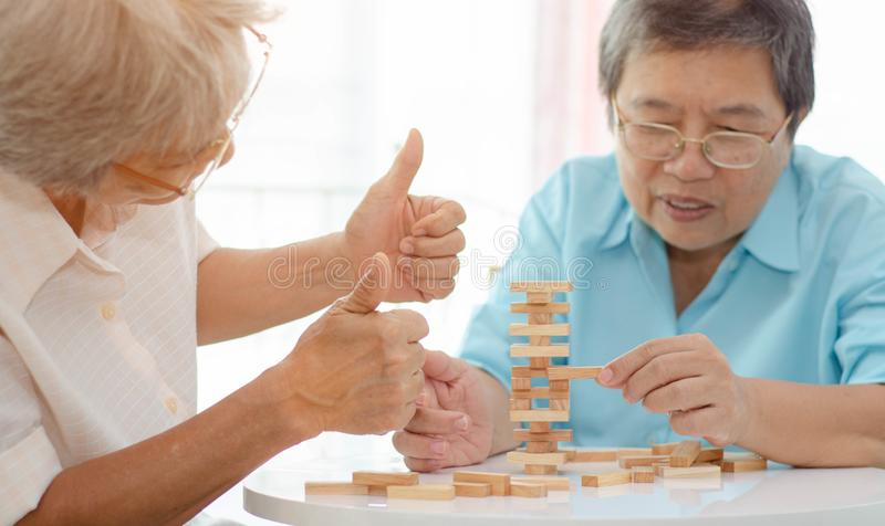 Elderly activities. Asian elderly women Wearing a blue shirt And friend are playing games Have fun in the morning at home in the room stock photo