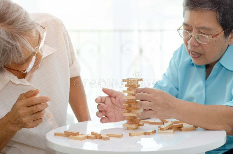 Elderly activities. Asian elderly women Wearing a blue shirt And friend are playing games Have fun in the morning at home in the room stock image