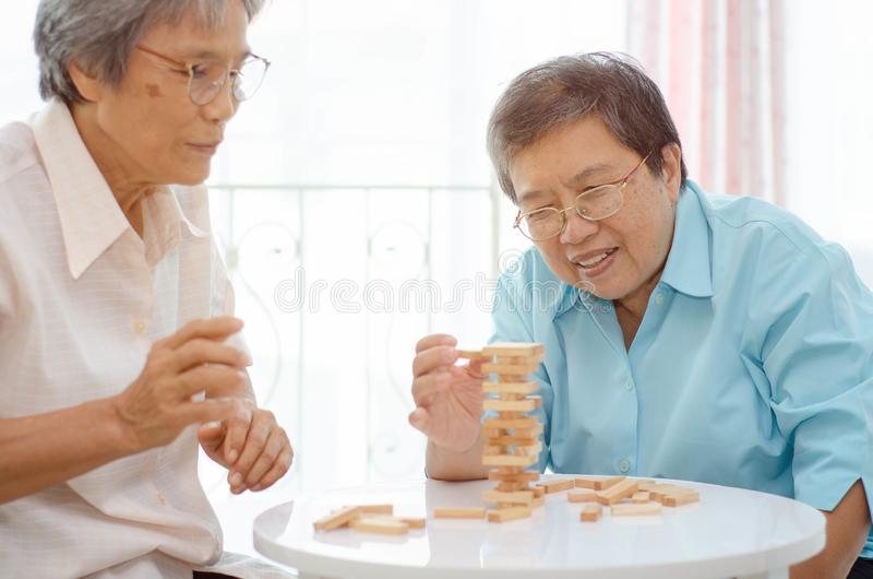 Elderly activities. Asian elderly women Wearing a blue shirt And friend are playing games Have fun in the morning at home in the room stock images