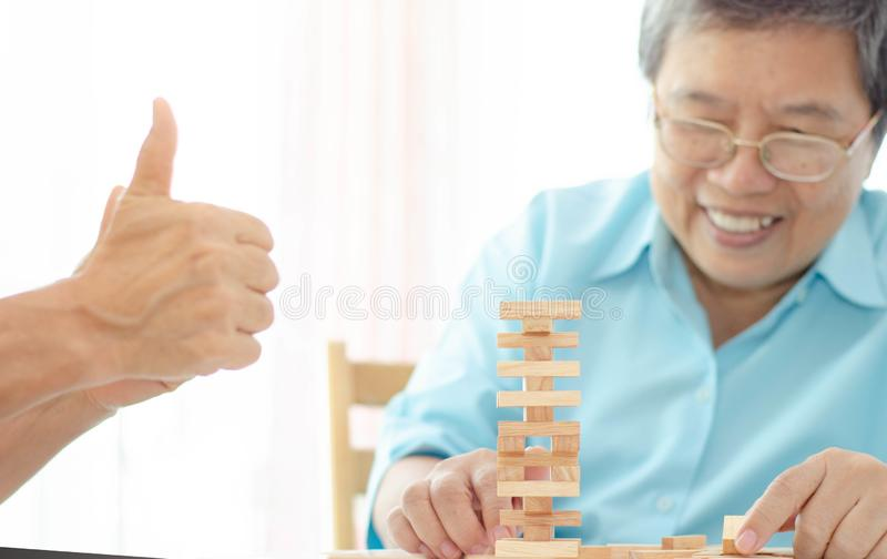 Elderly activities. Asian elderly woman Wearing a blue shirt And friend are playing games Have fun in the morning at home in the room stock photography