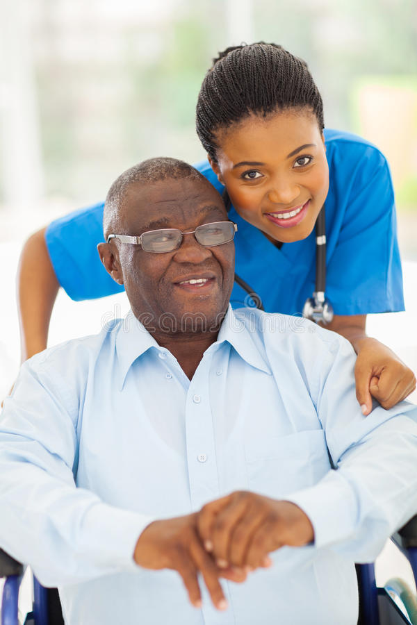 Elderly african man caregiver. Elderly african american men and caring young caregiver at home stock image