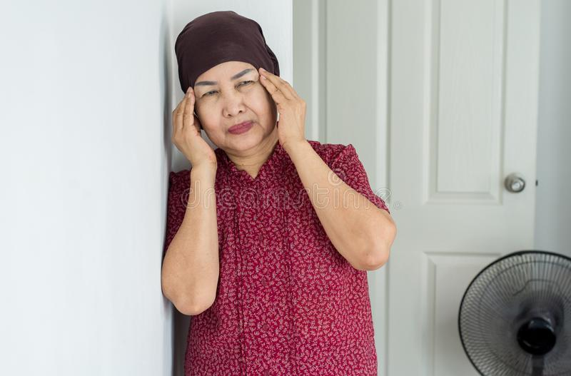 Elderly Asian woman depression of lonely have a headache at home,Mental disorder health care,World suicide prevention day concept stock photography