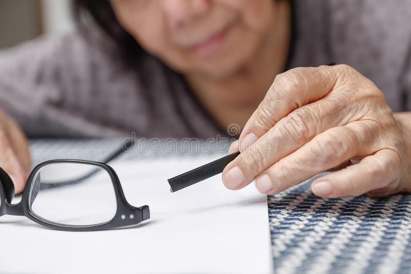 Elderly asian woman repair broken glasses royalty free stock photo