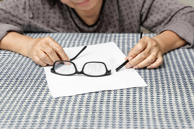 Elderly asian woman repair broken glasses stock photo