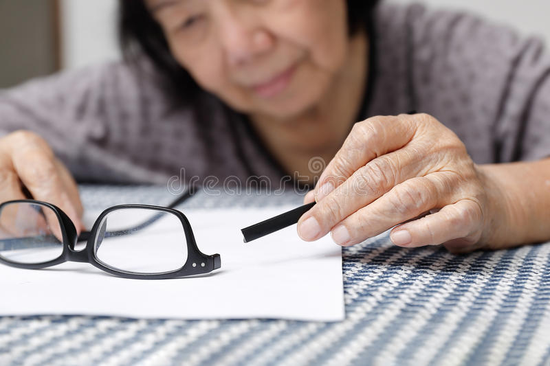 Elderly asian woman repair broken glasses royalty free stock photos