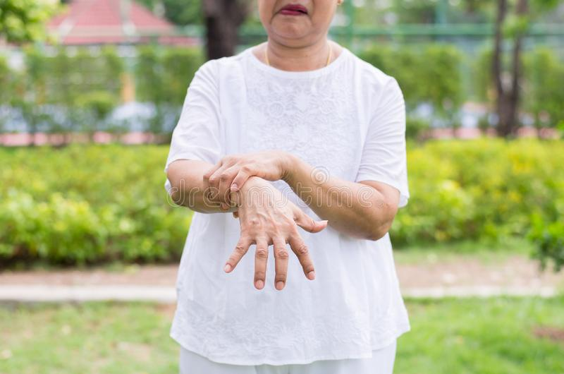Elderly asian woman suffering with parkinson`s disease symptoms royalty free stock photography