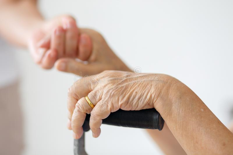 Elderly asian woman using a cane with caregiver take car. Elderly asian women using a cane at home with caregiver take care stock photo