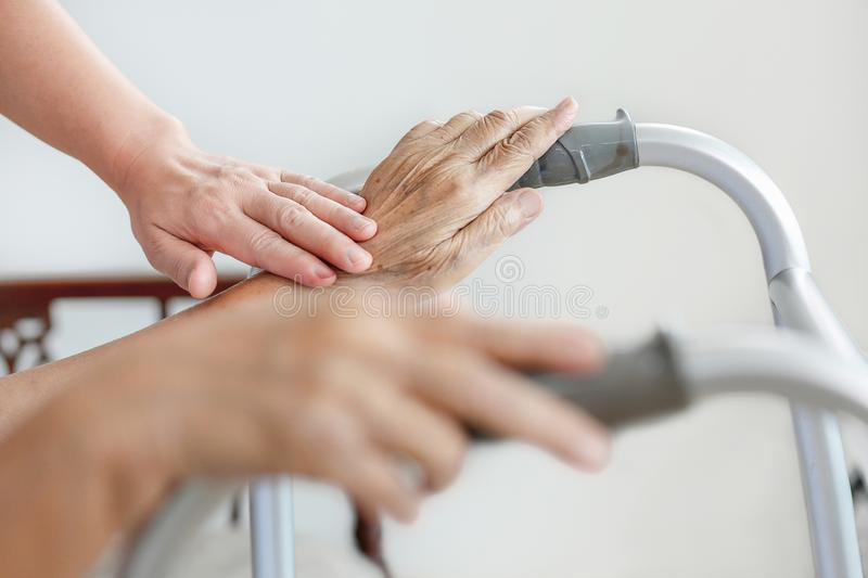 Elderly asian woman using a walker at home with caregiver stock images