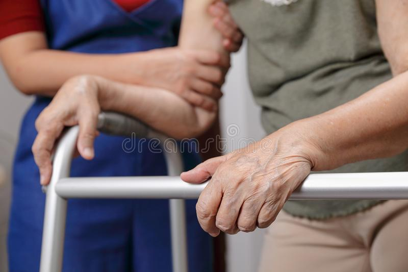 Elderly asian woman using a walker at home with daughter take ca. Elderly asian women using a walker at home with daughter take care at home royalty free stock image