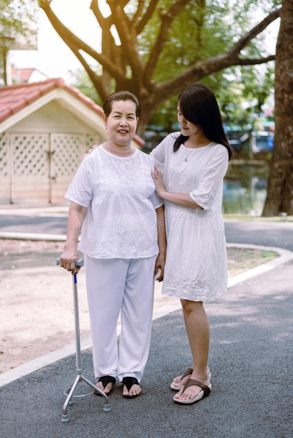 Elderly Asian woman walking to do physical with stick at park,Daughter take care and support,Elderly social asia concept. Elderly Asian women walking to do royalty free stock photo
