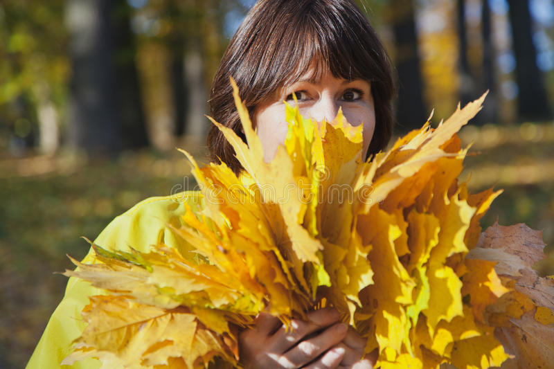 Elderly attractive woman hiding her face behind armful yellow au stock photos
