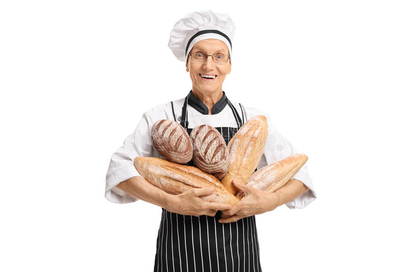 Elderly baker holding loaves of bread royalty free stock images