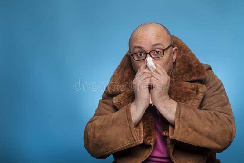 An elderly bald man in a fur coat is snuff his handkerchief,. On the blue background stock image