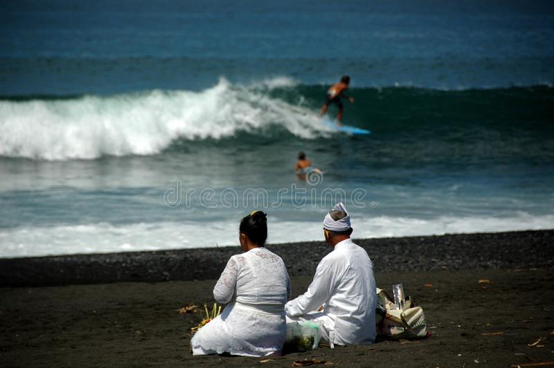 An Elderly Balinese Couple Getting Ready for Morning Ritual on a Beach royalty free stock image