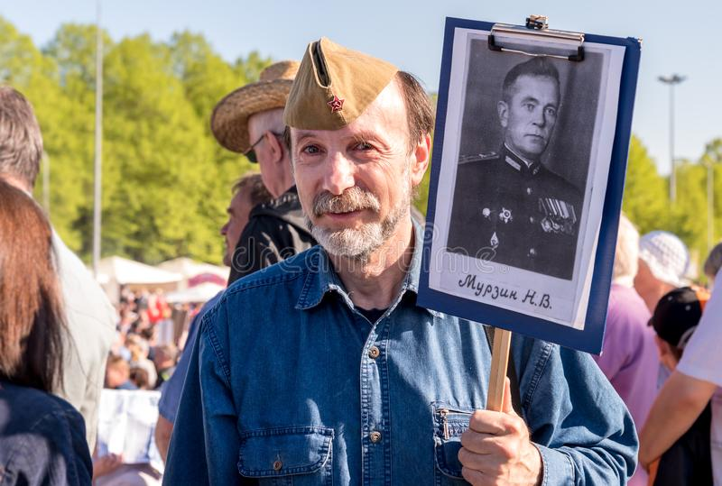 Elderly bearded man with a portrait of his relative in Immortal Regiment on annual Victory Day in the Victory park of Riga, Latvia. Riga, Latvia - May 9, 2018 stock image