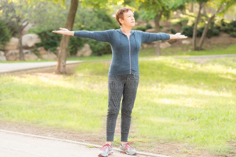 Elderly beautiful active happy woman in the morning in the autumn park doing sports exercises. royalty free stock images