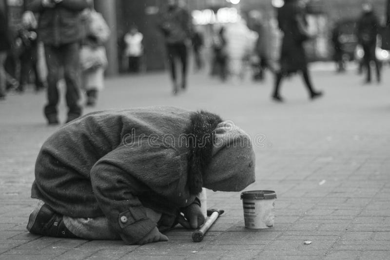 Elderly beggar woman begging on her knees on a city street. Beggars. Social problem. Black and white stock photos