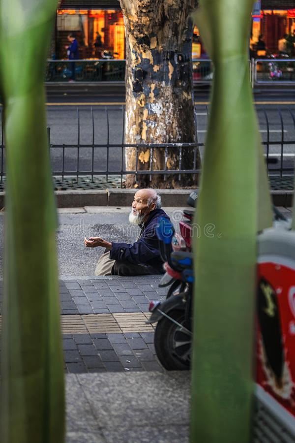 Elderly begging at the door of the supermarket. In March 2017, an old man was begging at the entrance of the supermarket in Confucius Temple Commercial Street stock photography