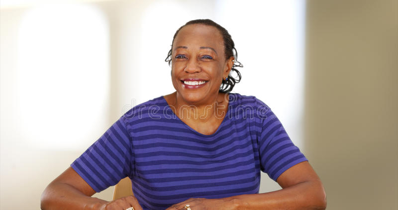 An elderly black woman smiling at the camera.  royalty free stock image