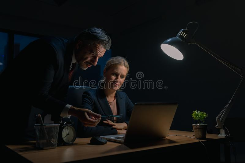An elderly business man is advising company employees at the office during overtime , Two businessmen are discussing and solving royalty free stock images