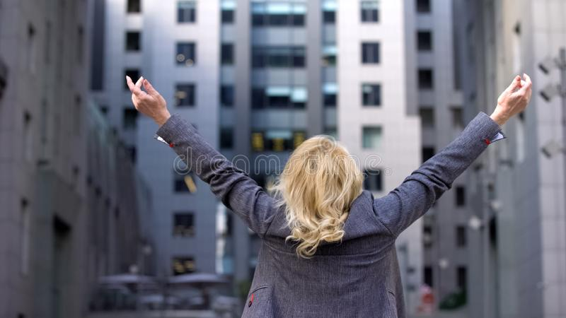 Elderly business woman standing back with raised hands up, career motivation royalty free stock image