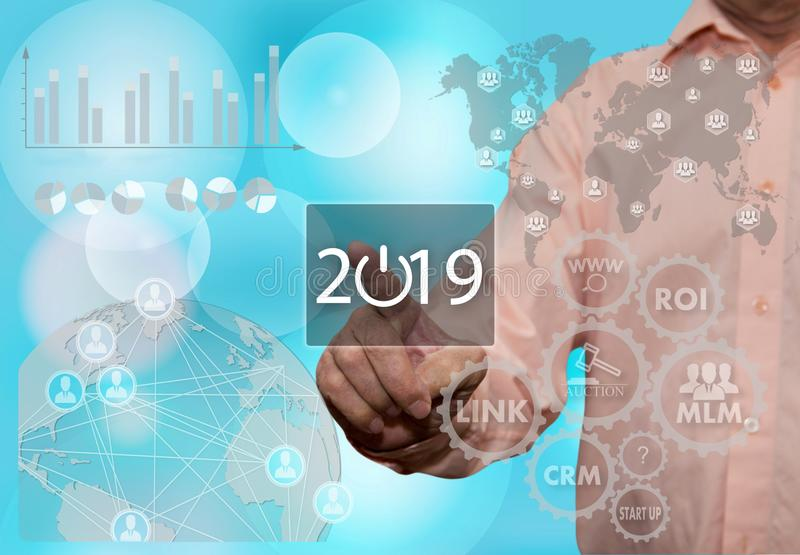 An elderly businessman chooses 2019 year on the touch screen wit stock photography