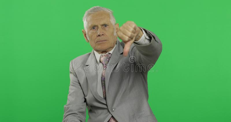 Elderly businessman giving thumb dow. Old man in formal wear showing thumb down stock photos