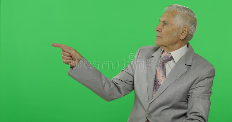 Elderly businessman points at something. Old man in formal wear on chroma key royalty free stock images