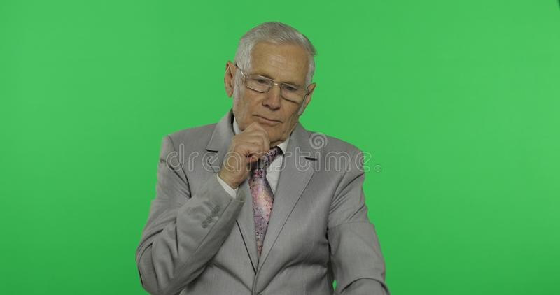 Elderly businessman in suit thinks about something. Old thoughtful senior man stock photos