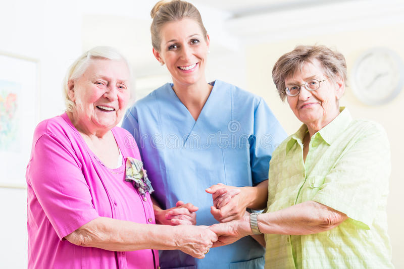 Elderly care nurse with two senior women royalty free stock image