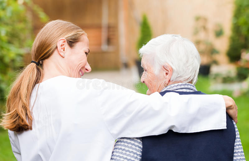 Elderly care. Young carer walking with the elderly women in the park royalty free stock photography