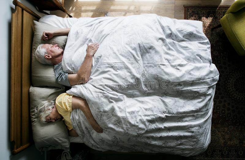Elderly Caucasian couple sleeping on the bed royalty free stock image