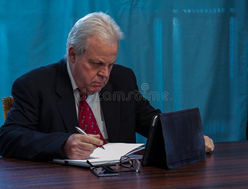 Elderly executive at boardroom table stock image