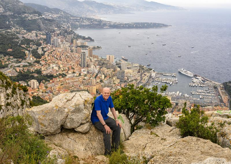 Elderly caucasian male Amerasian tourist posing on Tete de Chien, with a vew of Monaco in the background. stock photos