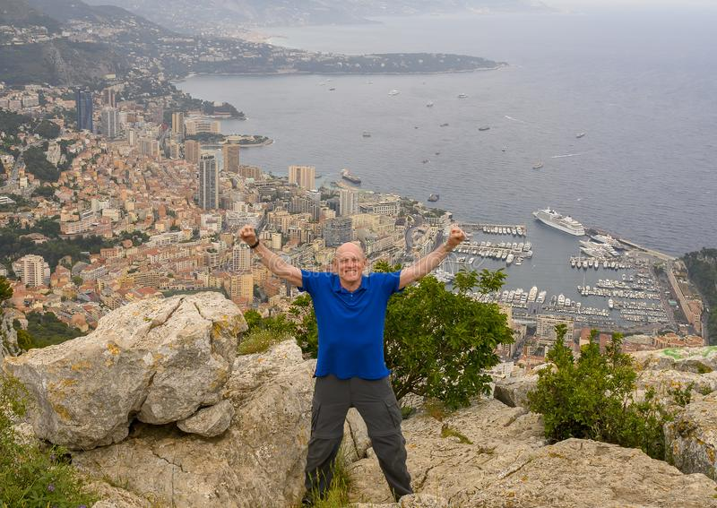 Elderly caucasian male Amerasian tourist posing on Tete de Chien, with a vew of Monaco in the background. royalty free stock photos