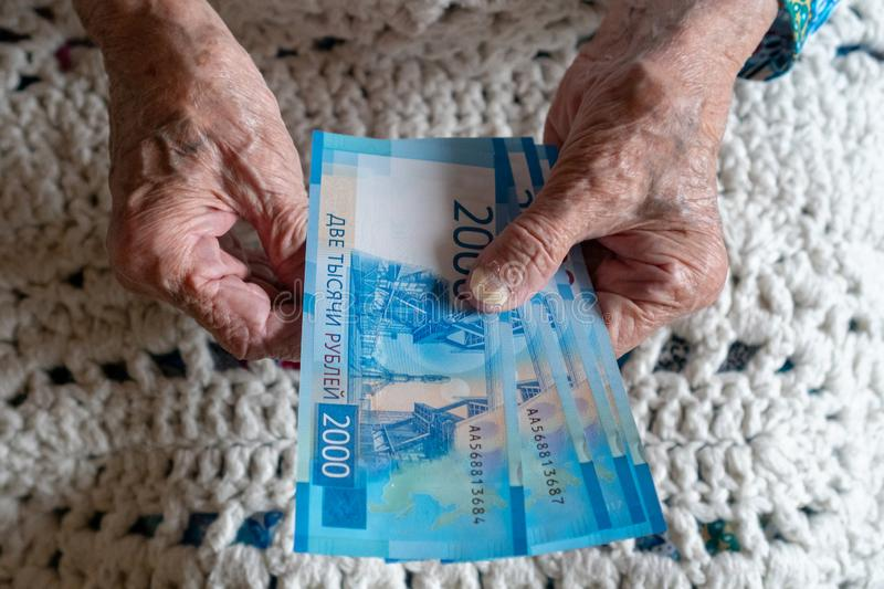 Elderly caucasian woman 90 eyears old counting money in her hands stock photos