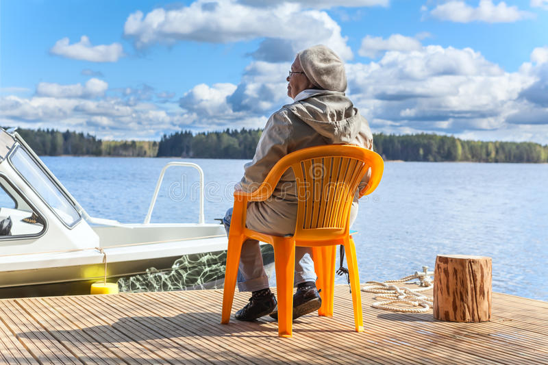 Elderly Caucasian woman relaxing at lake on pier stock photography