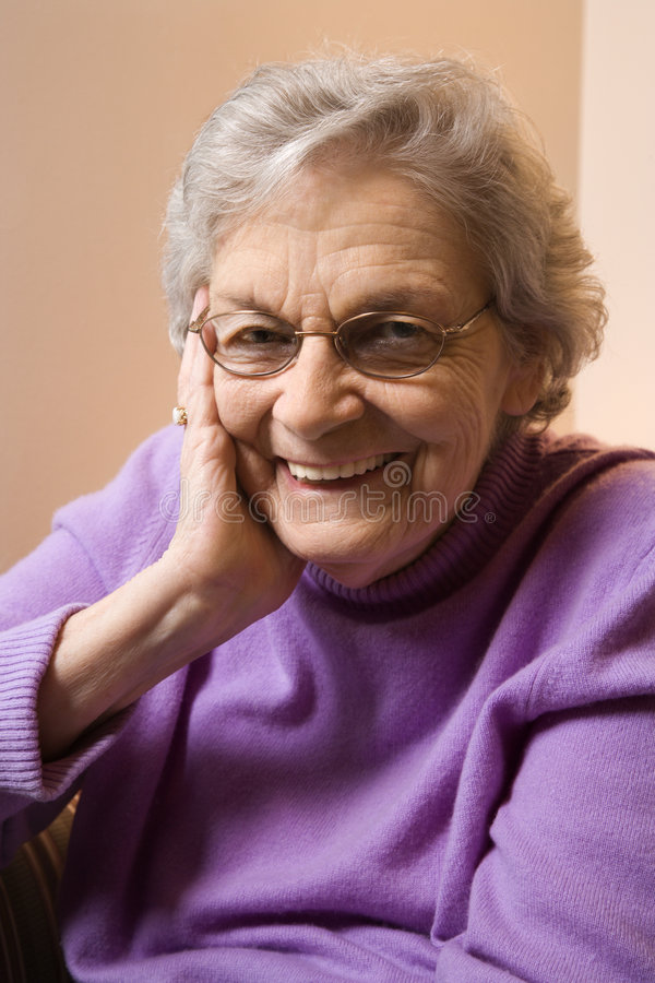 Elderly Caucasian woman smiling. Elderly Caucasian woman smiling with hand on face stock images
