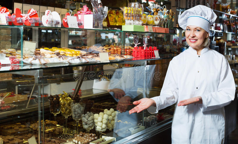 Elderly cheerful positive seller with dark and white chocolates stock photo