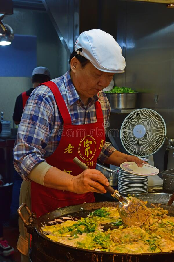An Elderly Chef cooking at the popular Yuan Huan Bian Restaurant famous for its oyster omelette. Taiwan specifically Taipei is well known for food street heaven