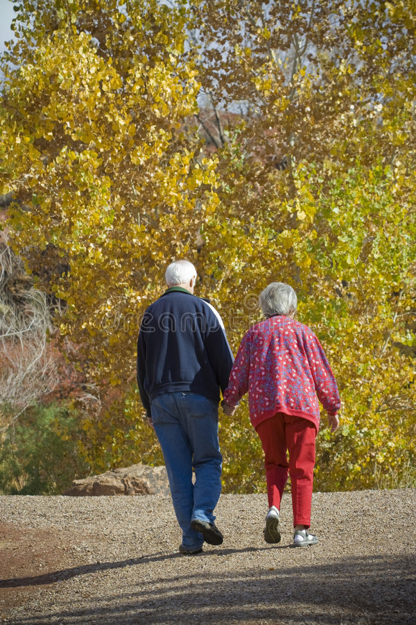 Elderly Couple. An older retired couple take a walk together on a autumn day as they enjoy their golden years together stock images
