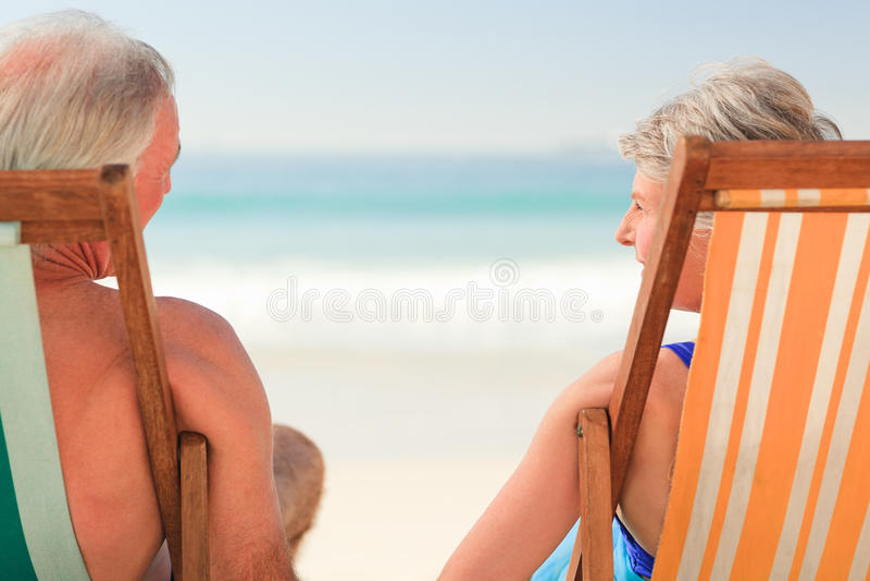 Elderly couple at the beach stock image