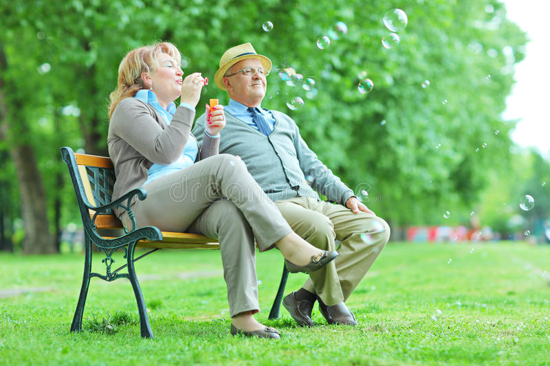 Elderly couple blowing bubbles in park stock photo