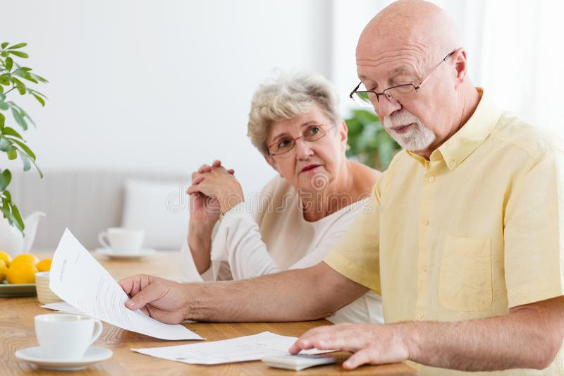 Elderly couple calculating costs of household. Senior people wit royalty free stock photos
