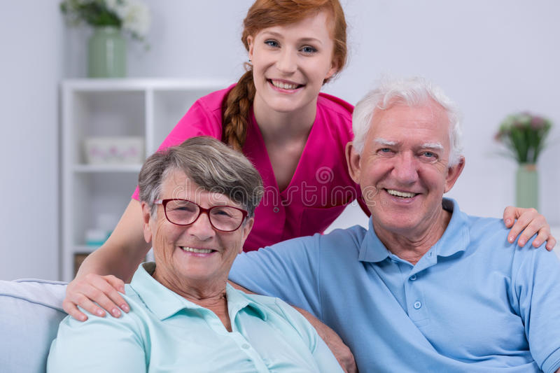 Elderly couple and caregiver. Happy elderly couple and young caregiver standing behind her stock images