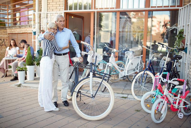 Elderly couple choosing new bicycle in bike shop stock photos