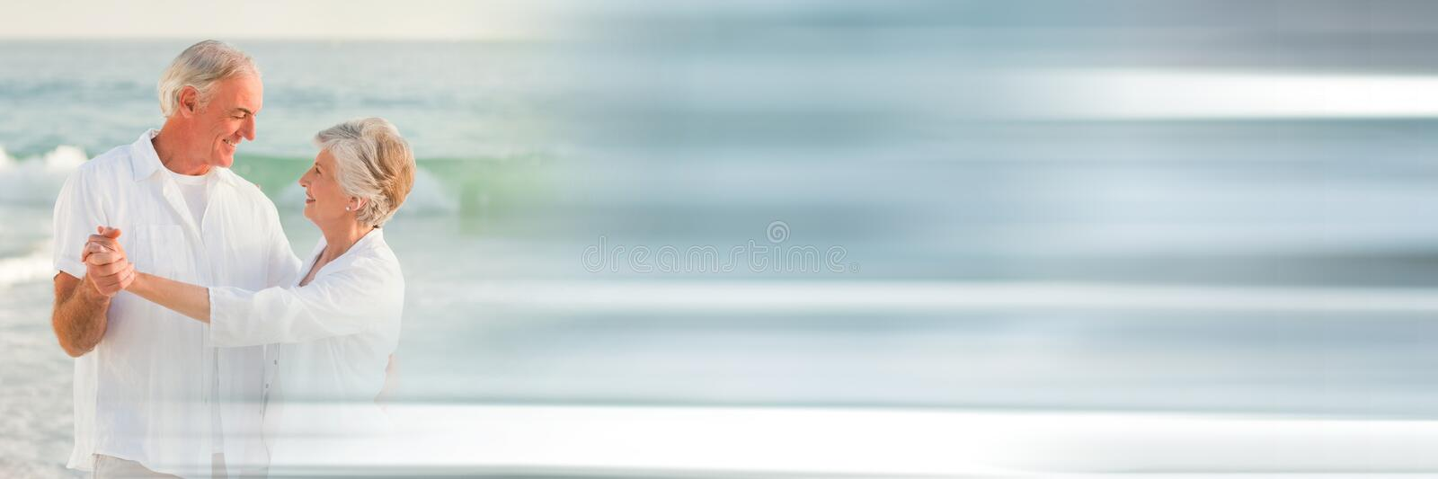 Elderly couple dancing on beach with blurry grey transition royalty free stock images