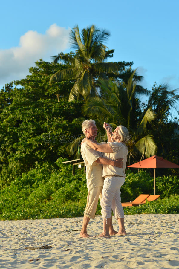 Elderly couple dancing at tropical beach stock photography